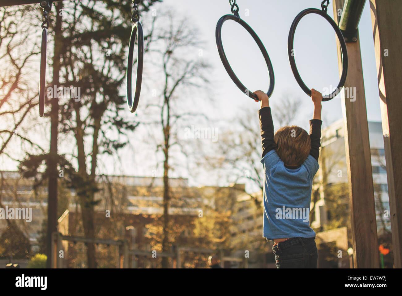 Boy hanging from sonne au jeu pour enfants Photo Stock
