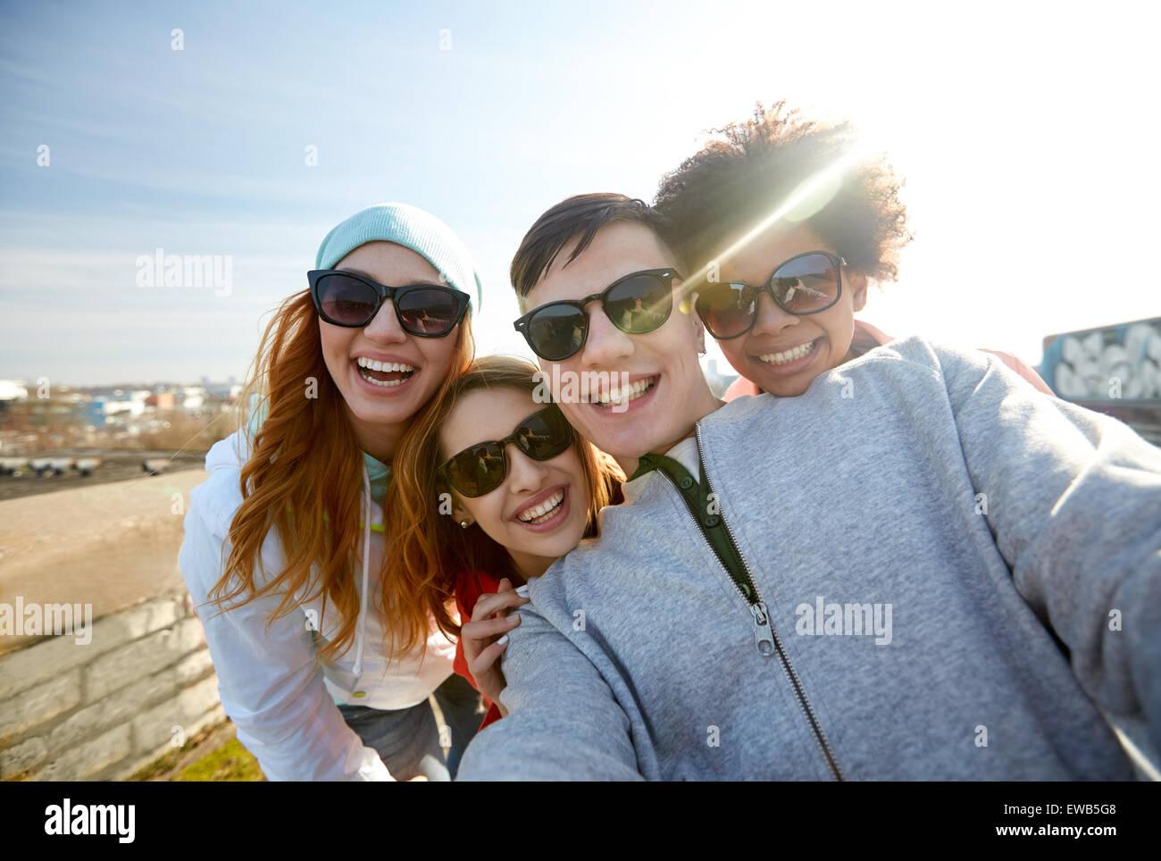 Groupe d'amis heureux de prendre sur selfies street Photo Stock