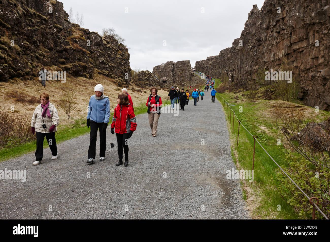 Les touristes à pied à travers la ligne de faille Almannagja dans la dorsale médio-atlantique plaque Photo Stock