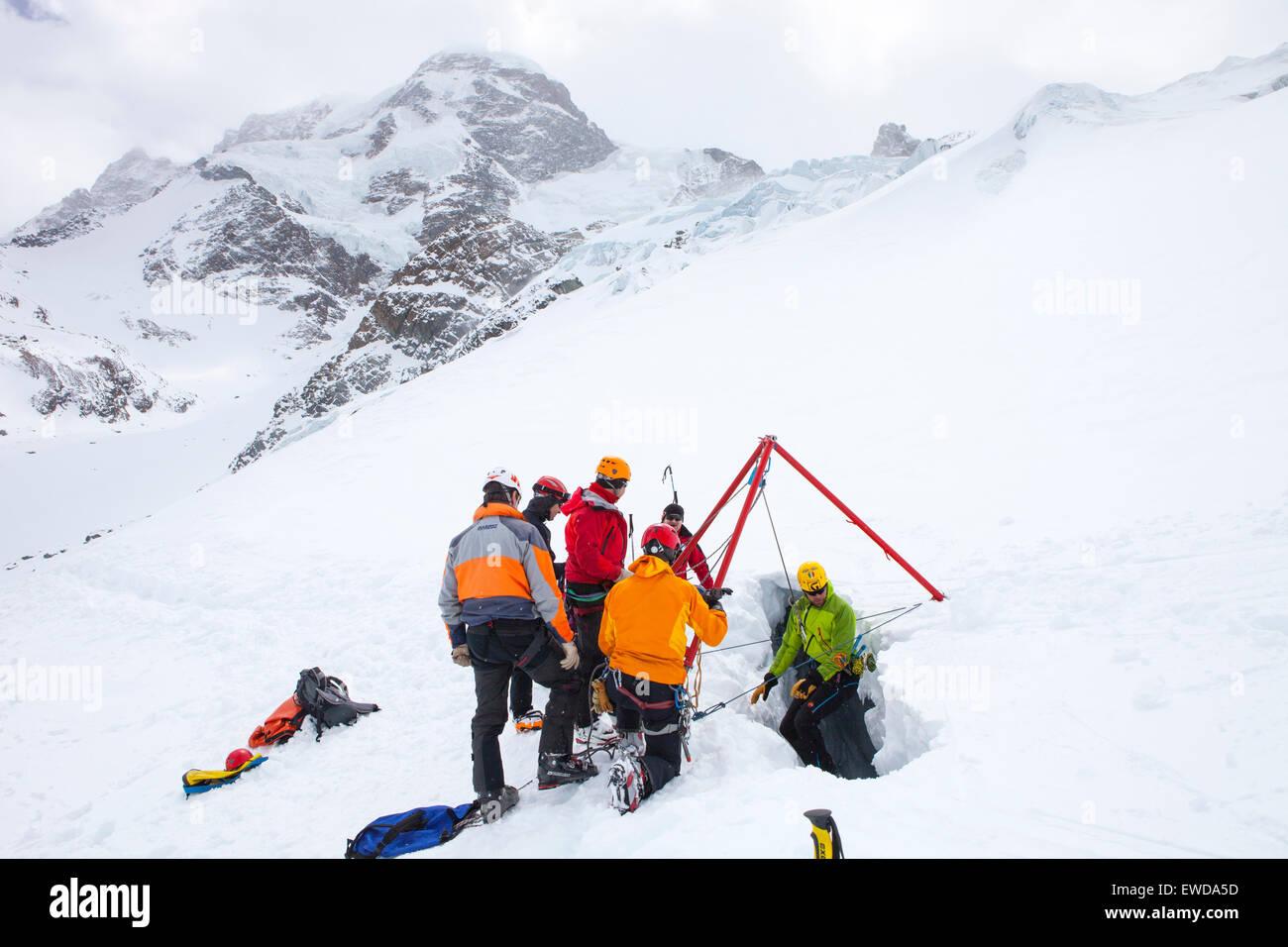 Un technicien de sauvetage en montagne est en ordre décroissant dans une crevasse. Lorsqu'un skieur se Photo Stock