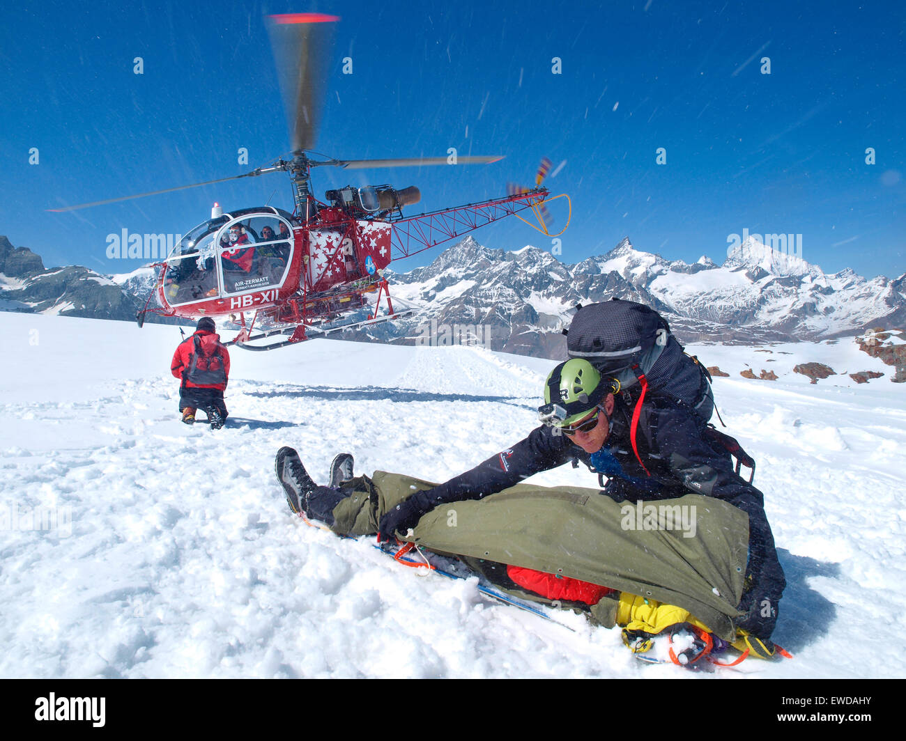Le personnel de secours en montagne est d'aider un alpiniste blessé dans les Alpes suisses. Un ambulancier Photo Stock