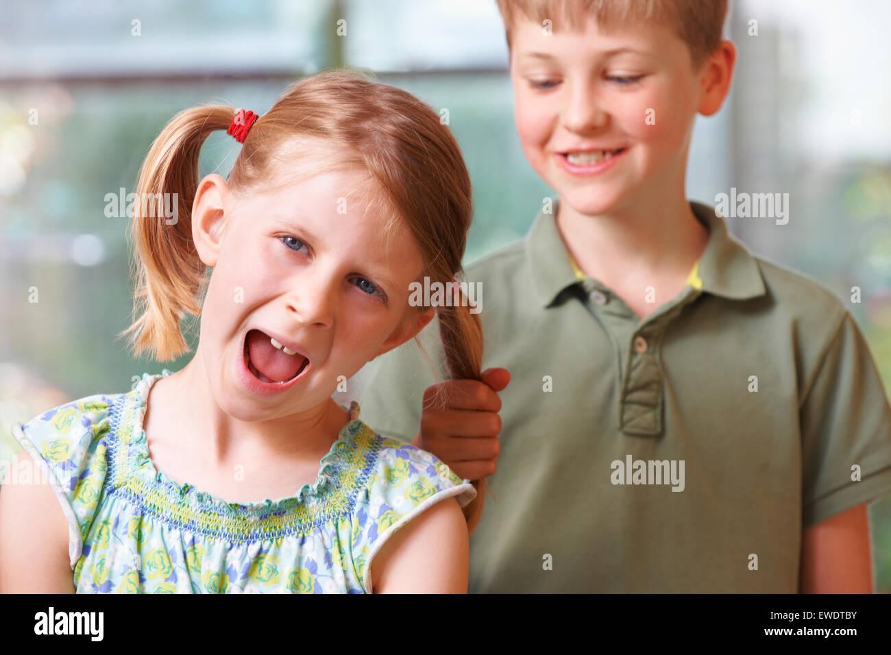 Garçon Fille en tirant les cheveux de l'intimidation Photo Stock