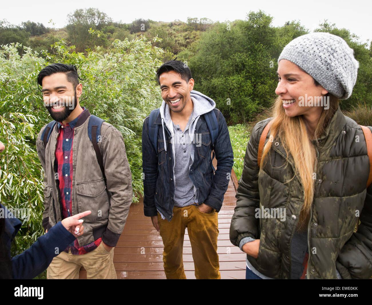 Souriante jeune femme et deux jeunes hommes marchant dans un parc Photo Stock