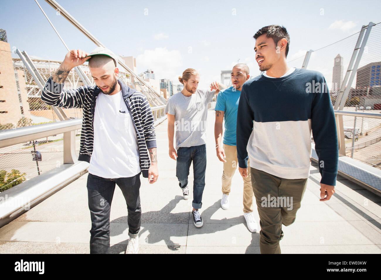 Groupe de jeunes hommes marchant le long de la passerelle Photo Stock