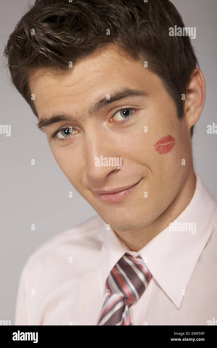 Young caucasian businessman with lipstick kiss marque sur sa joue Photo Stock