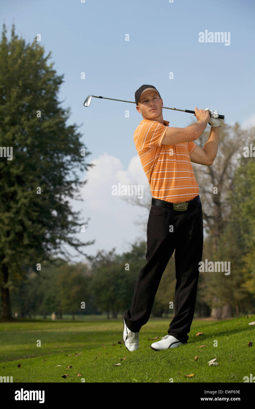 Jeune homme swinging golf club Photo Stock