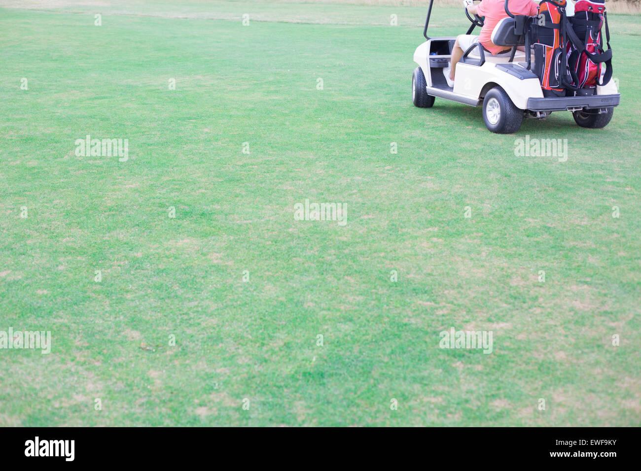 La section basse de l'homme d'âge moyen roulant chariot de golf Photo Stock