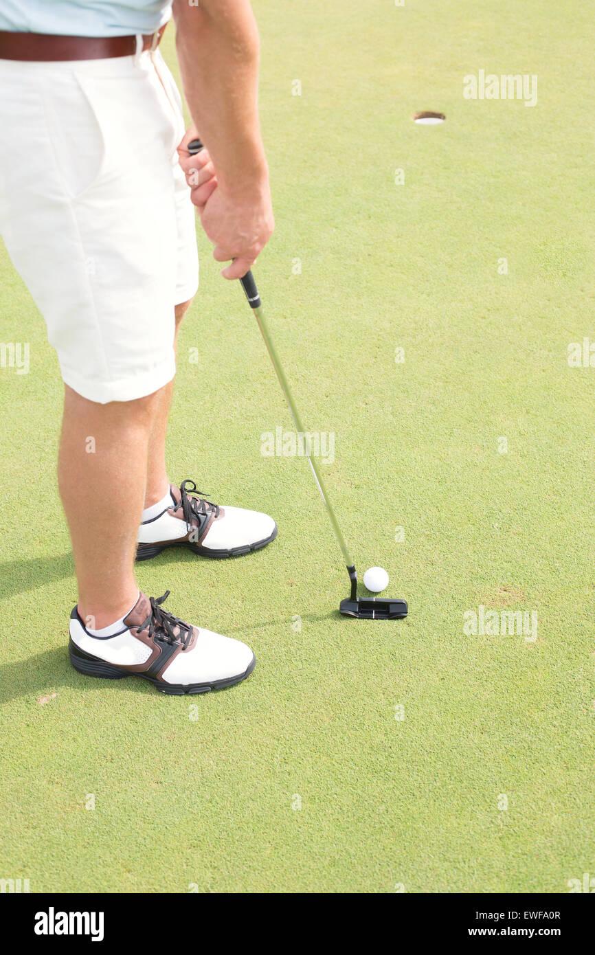 La section basse de l'homme jouer au golf au cours Photo Stock