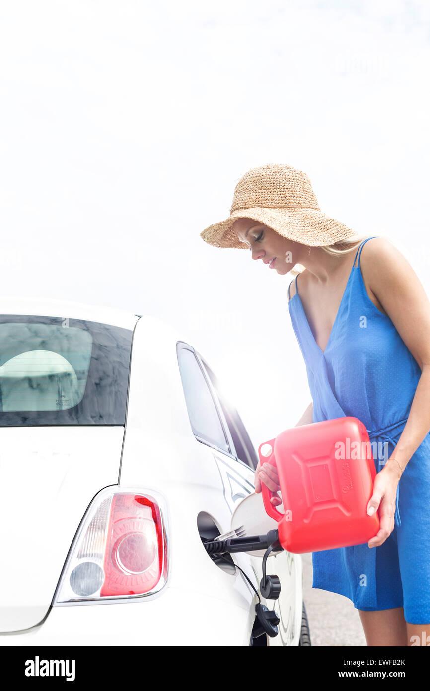 Woman refueling car contre ciel clair aux beaux jours Photo Stock