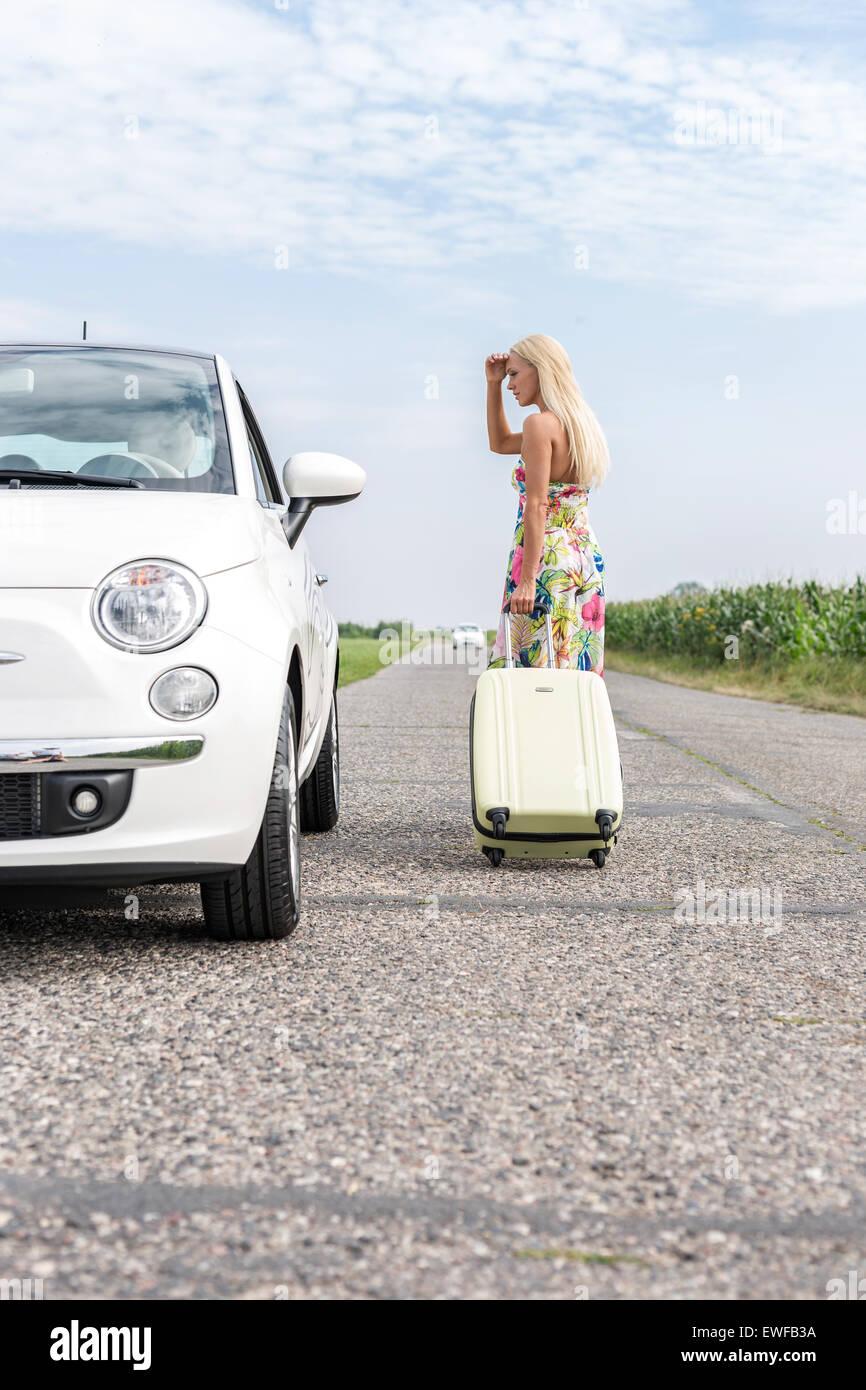 Woman looking at ventilés car tout en tirant une assurance on country road Photo Stock