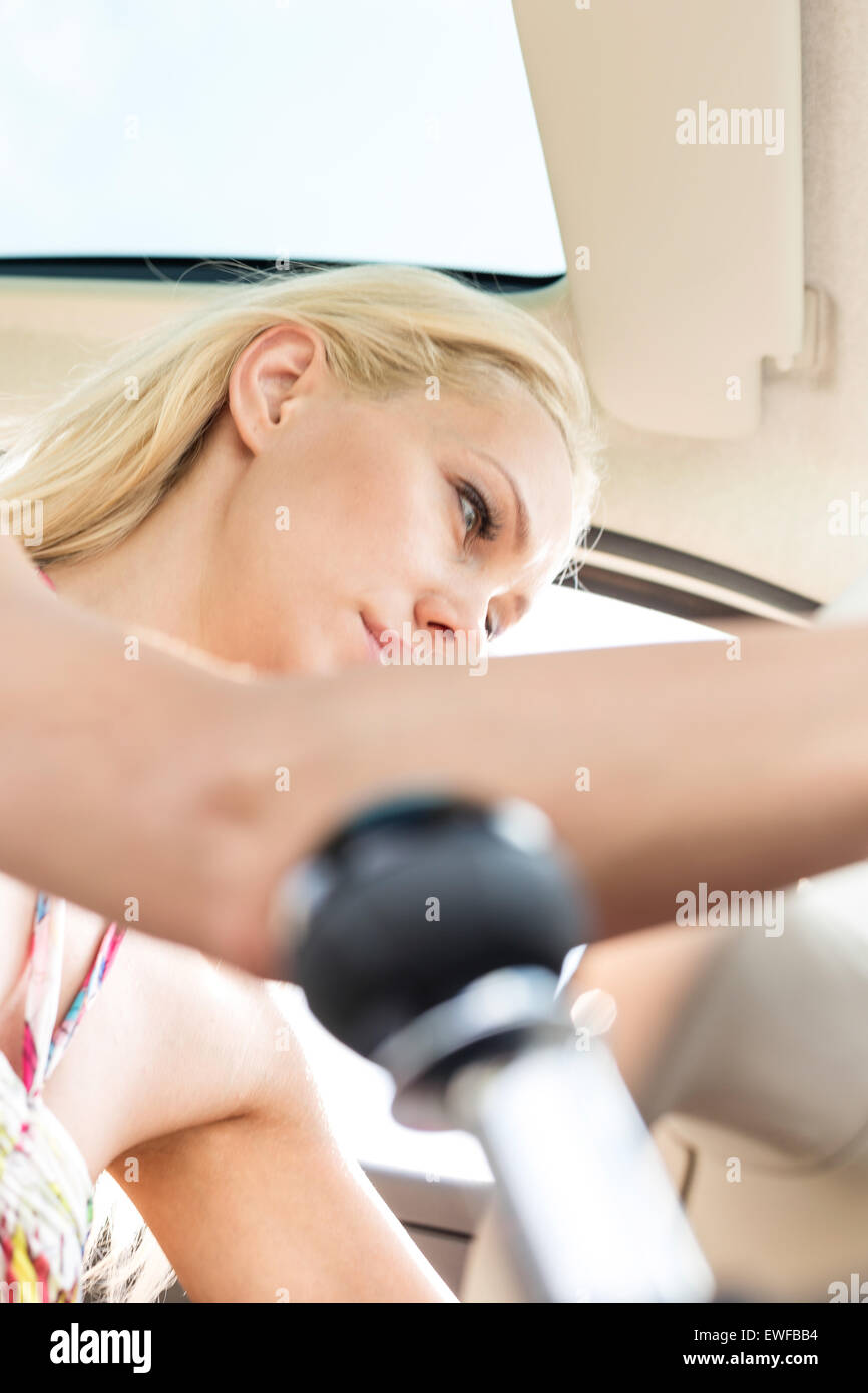 Low angle view of woman sitting in car Photo Stock