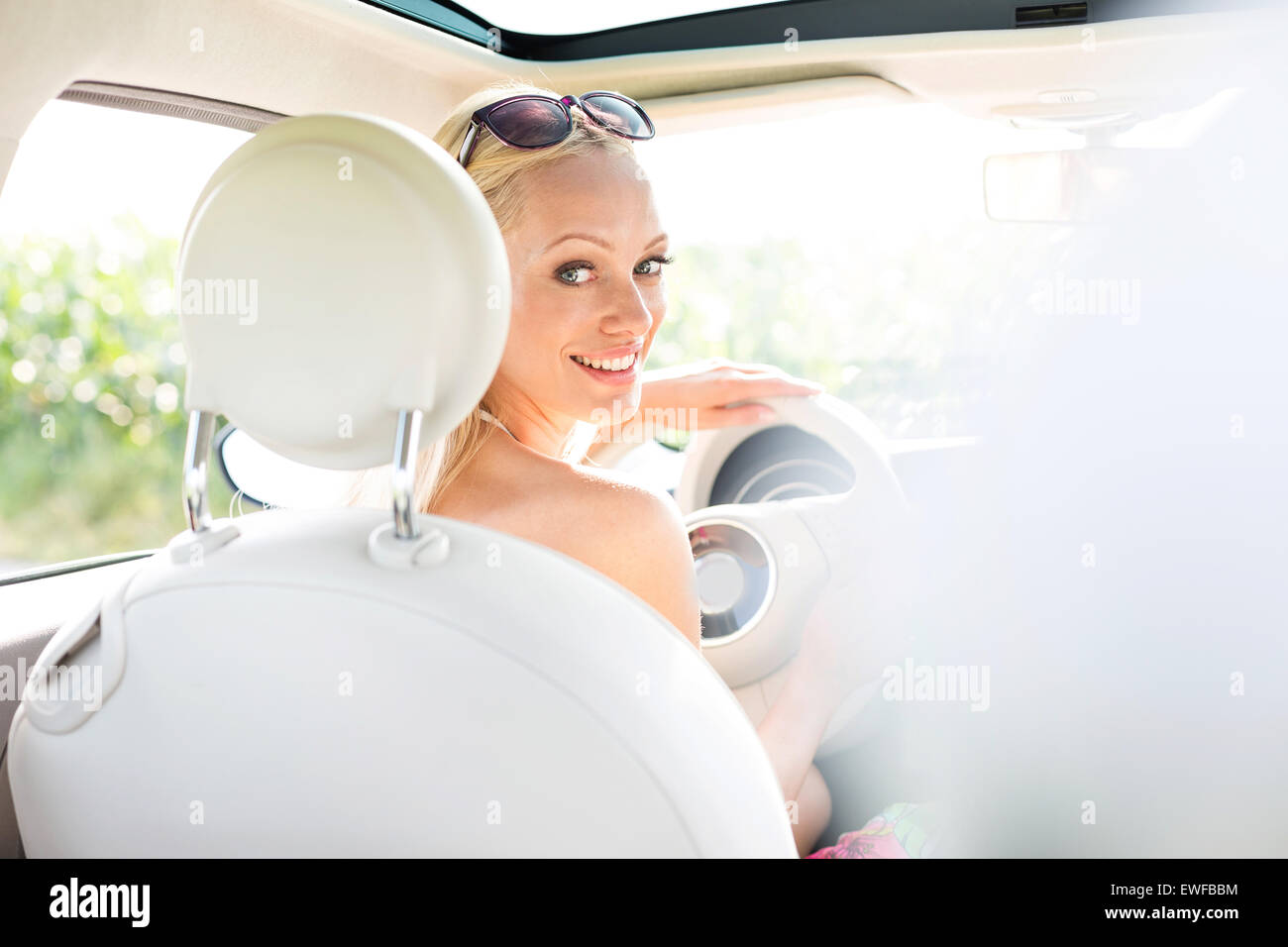 Vue arrière portrait of happy woman driving car Photo Stock