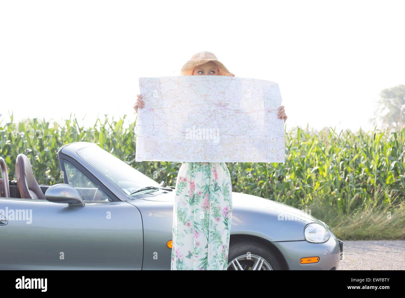 Femme se cachant le visage avec la carte par contre convertible ciel clair Photo Stock