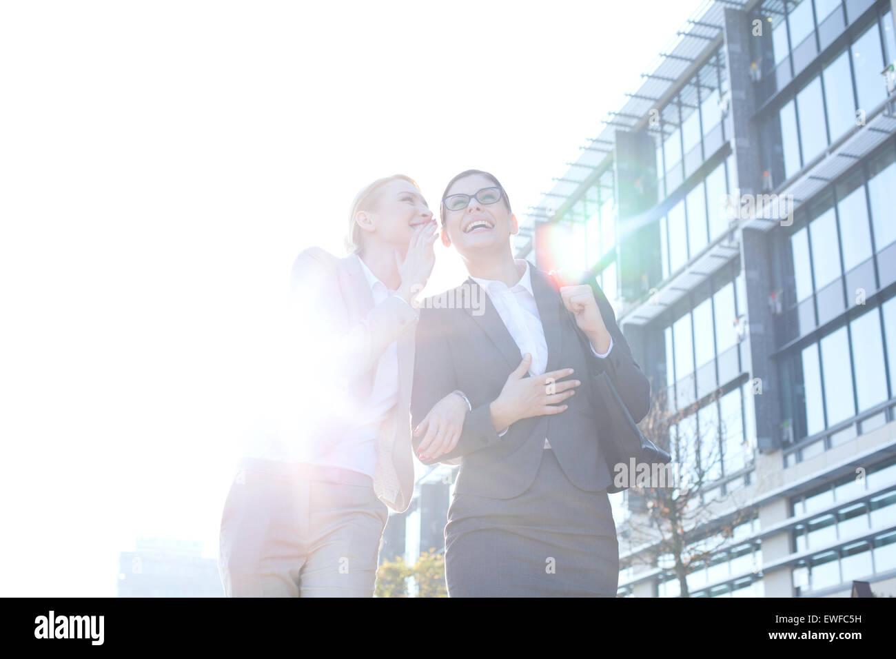 Happy businesswoman chuchotant à l'oreille de collègue à l'extérieur de bâtiment Photo Stock
