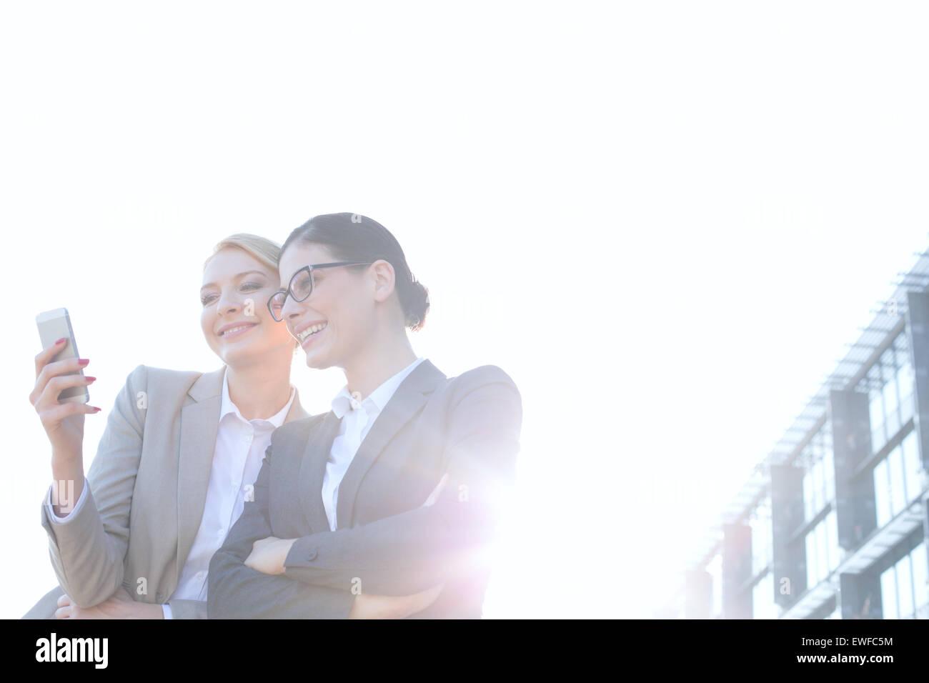 Low angle view of businesswomen using smart phone contre ciel clair aux beaux jours Photo Stock