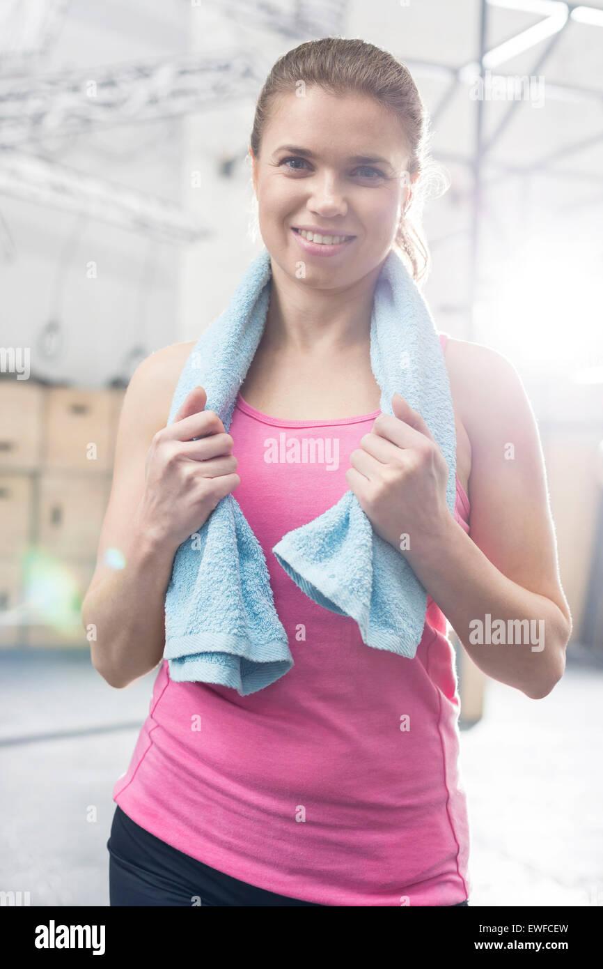 Portrait de femme heureuse avec une serviette autour du cou dans l'article de sport crossfit Photo Stock