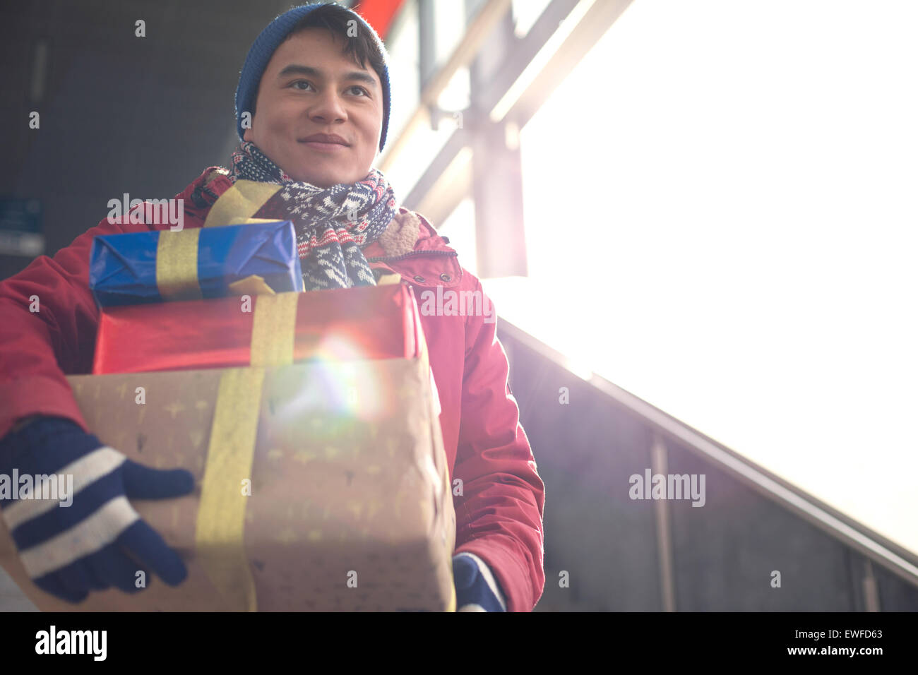Low angle view of smiling man holding gifts by window Photo Stock