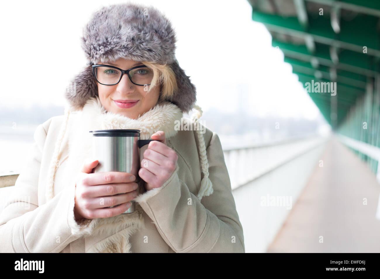 Portrait of smiling woman in vêtements chauds holding de boisson fraîche isolé Banque D'Images