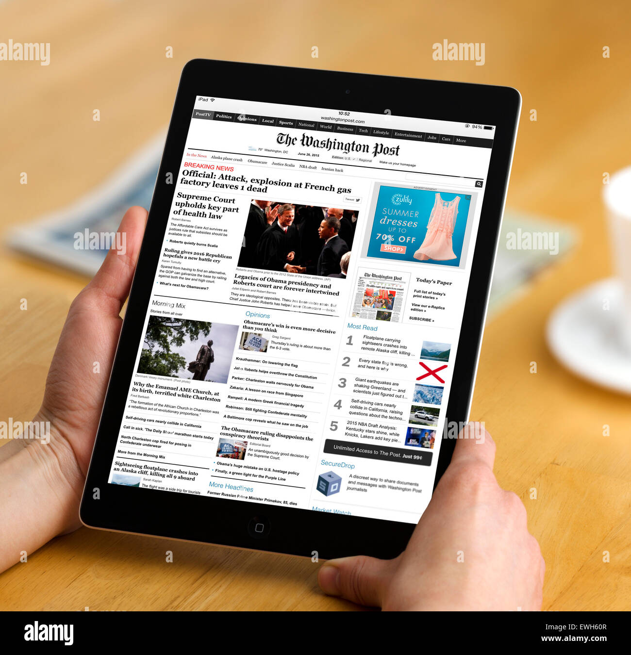 La lecture de l'édition internet du Washington Post, journal en ligne sur un Apple iPad Air Photo Stock