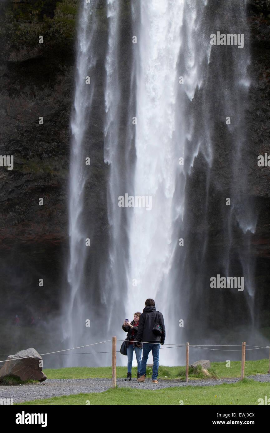 Des touristes posent pour des photos en face de la cascade de Seljalandsfoss Islande Photo Stock