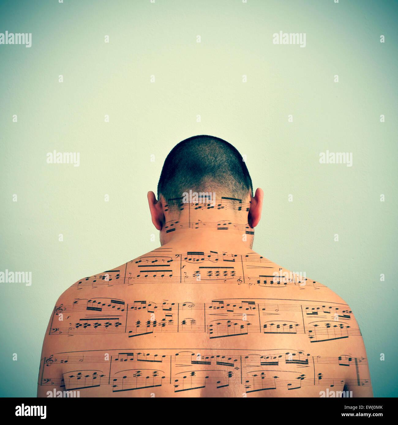 Un jeune homme de race blanche avec une partition de musique, dans son dos, avec un effet rétro Photo Stock
