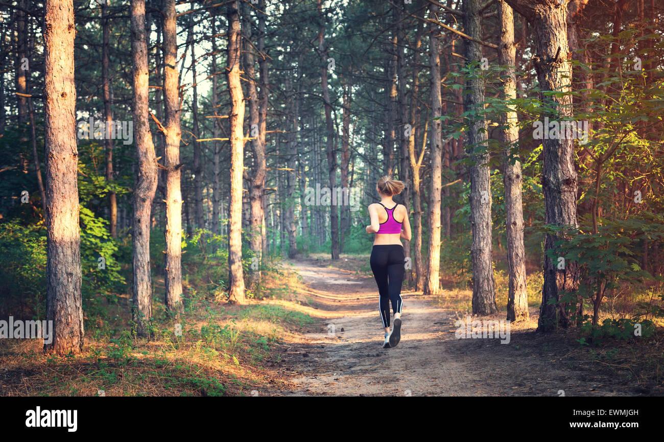 Jeune femme tournant sur un chemin rural au coucher du soleil en été. Fond sports Lifestyle Photo Stock