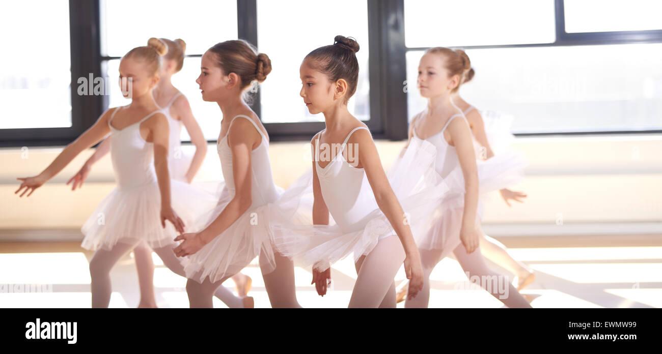 Groupe de jeunes ballerines effectuant un ballet chorégraphié comme ils s'entraînent ensemble Photo Stock