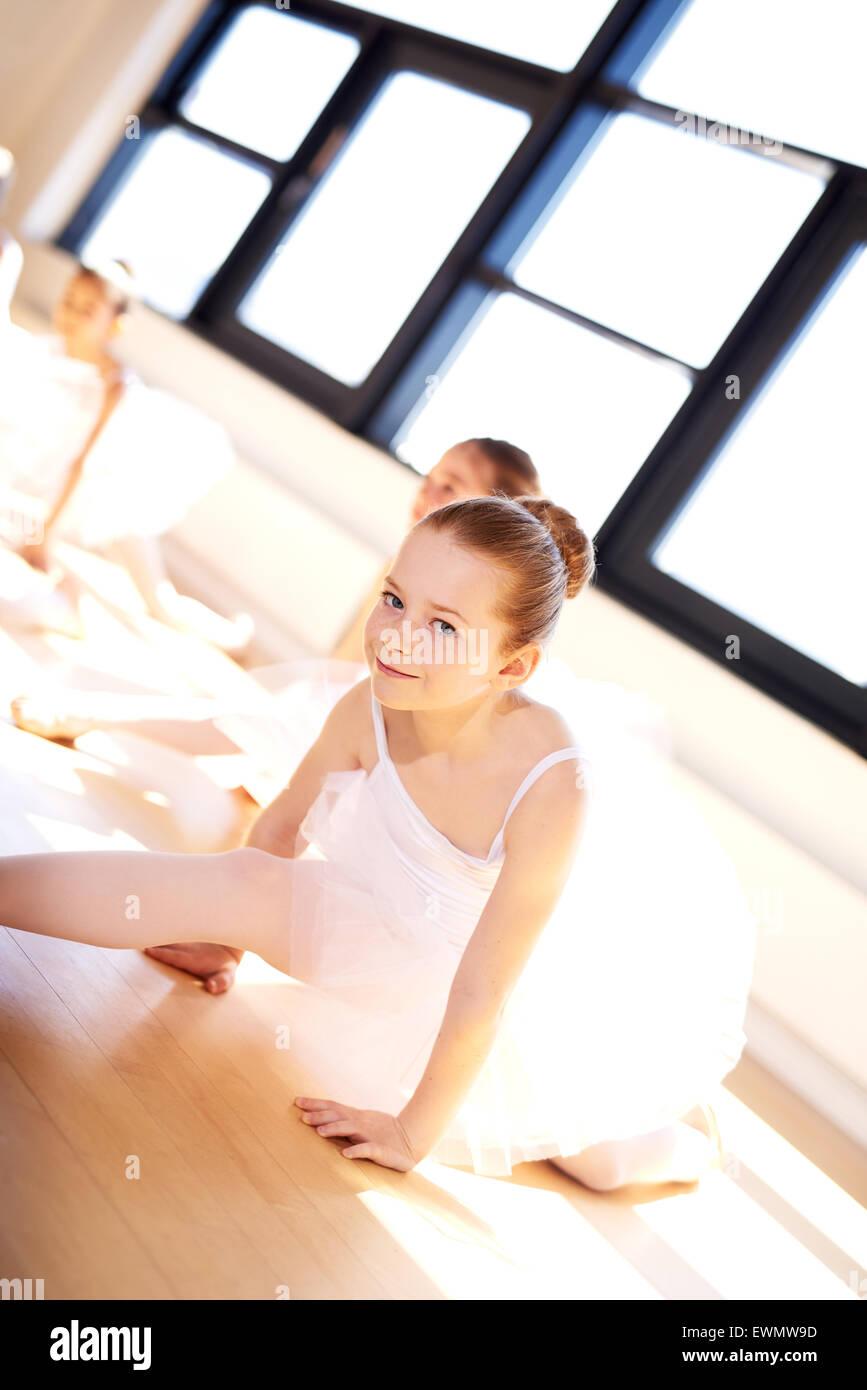 Jolie petite ballerine en Tutu blanc, partager ses jambes sur le plancher tout en regardant la caméra lors Photo Stock