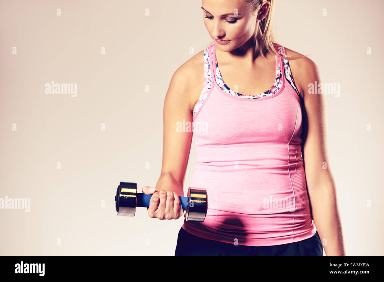 Young woman working out haut du corps, faisant un biceps curl. Photo Stock