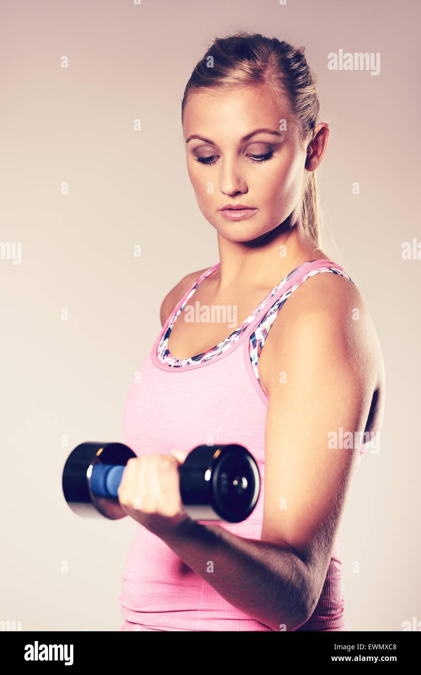 Jeune femme travaillant à son corps faisant un biceps curl. Photo Stock