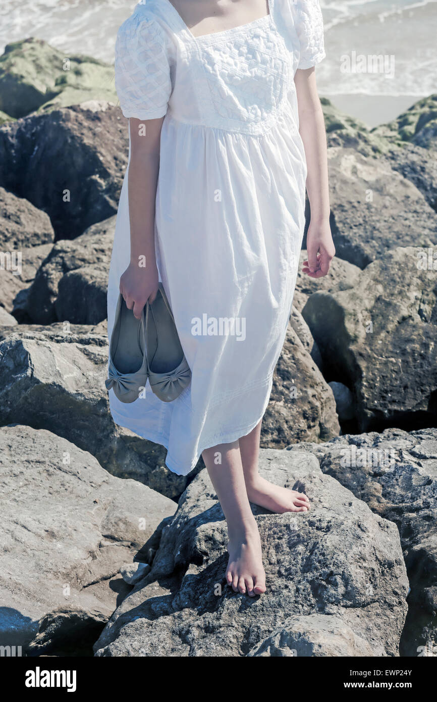 Une fille se tient pieds nus sur un rocher au bord de la mer, tenant ses souliers dans sa main Photo Stock