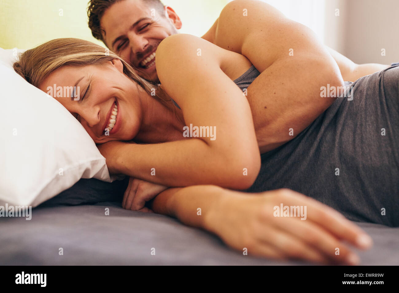 Image de cute young couple in love lying on bed. L'homme réveille sa femme en matinée. Photo Stock