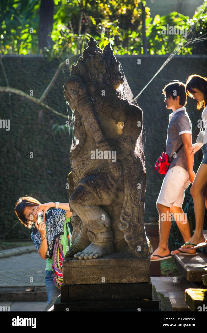 Les touristes asiatiques marcher devant Dvarapala statue au temple Tirta Empul complexe. Reynold © Sumayku Photo Stock