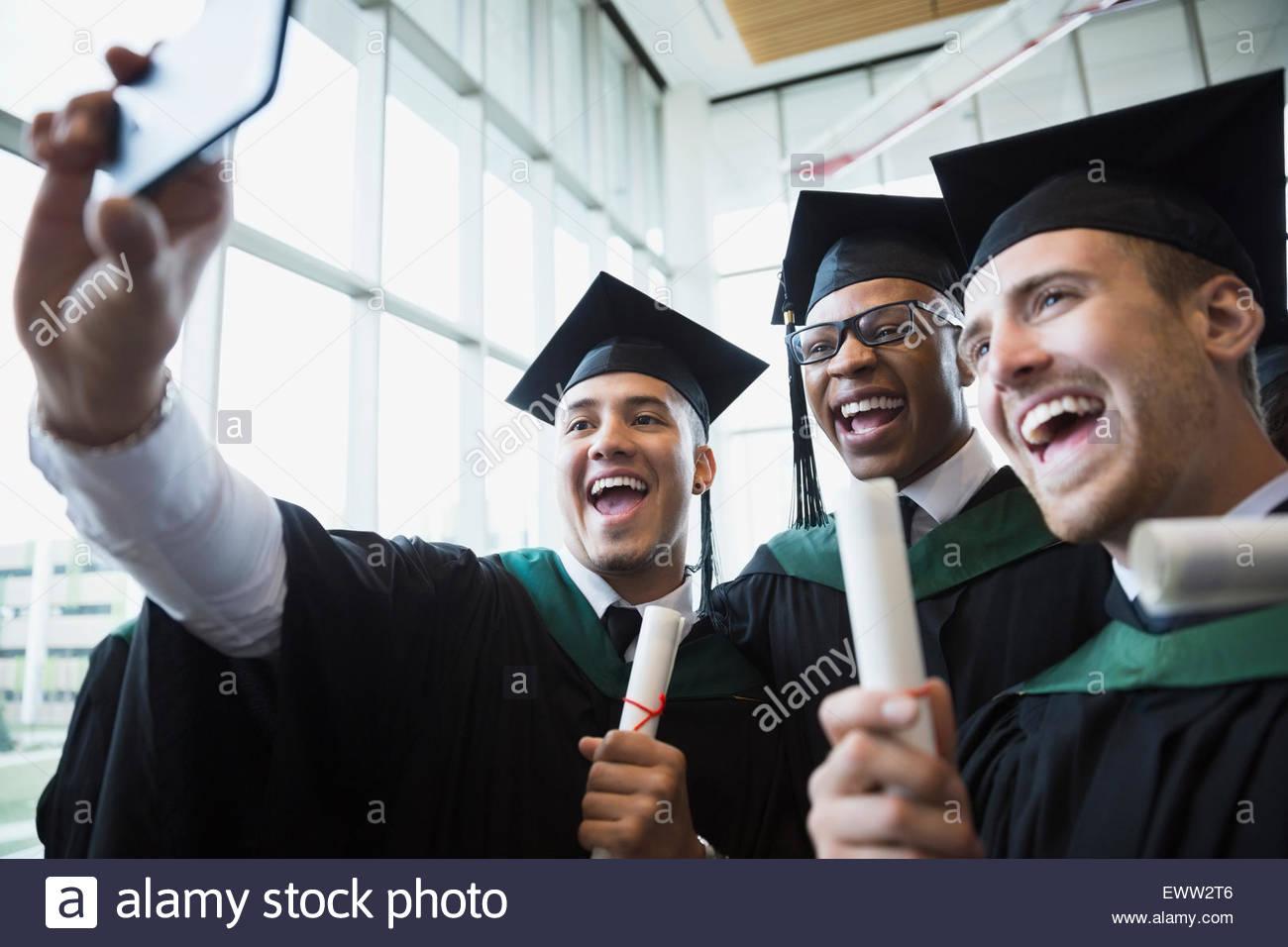 Les diplômés de collège enthousiastes cap and gown selfies en tenant Photo Stock