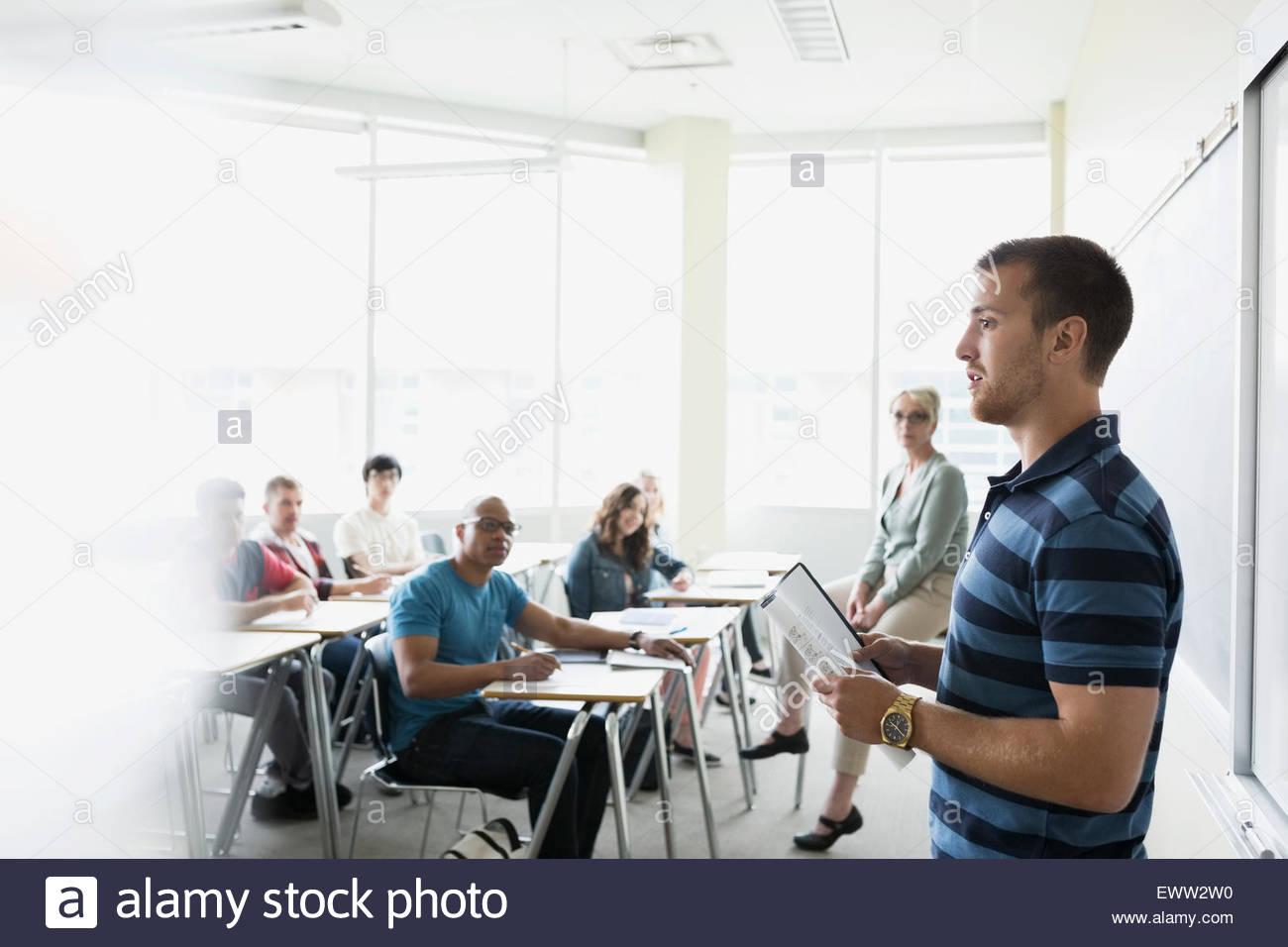 Le professeur et camarades regardant étudiant présentation donner Photo Stock