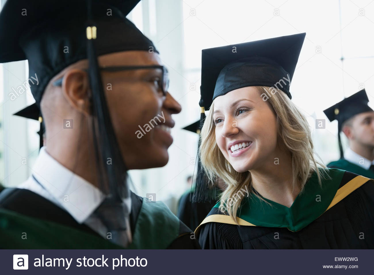 Smiling college graduates in cap and gown Photo Stock