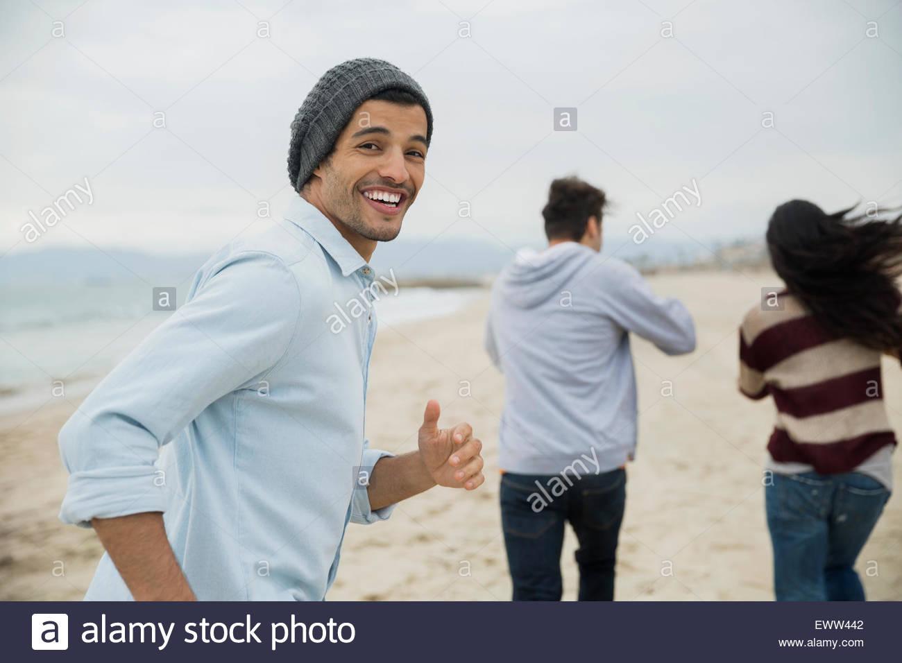 Portrait smiling man running avec des amis on beach Photo Stock