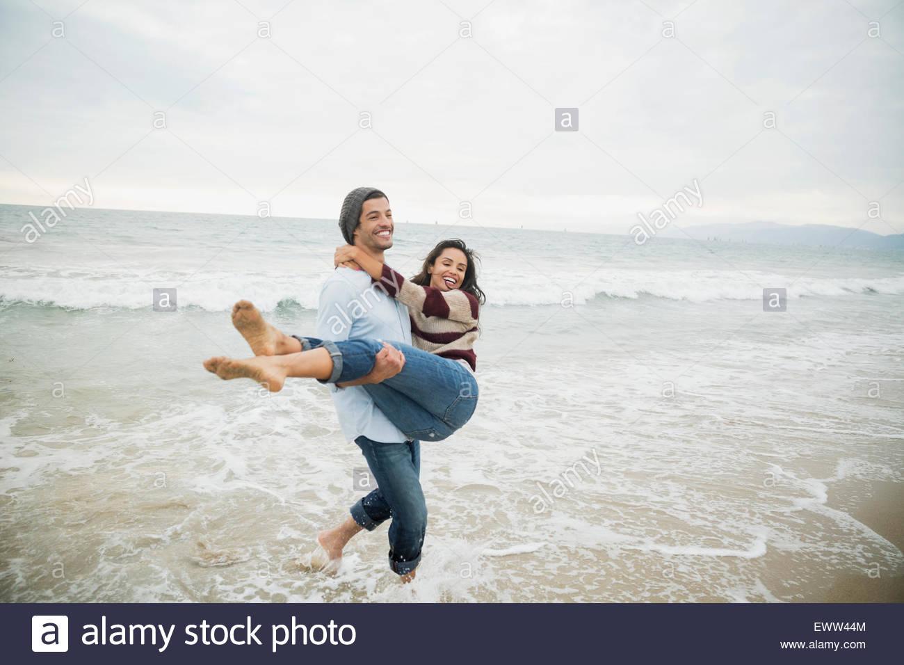Copain copine comptable ludique dans océan surf Photo Stock