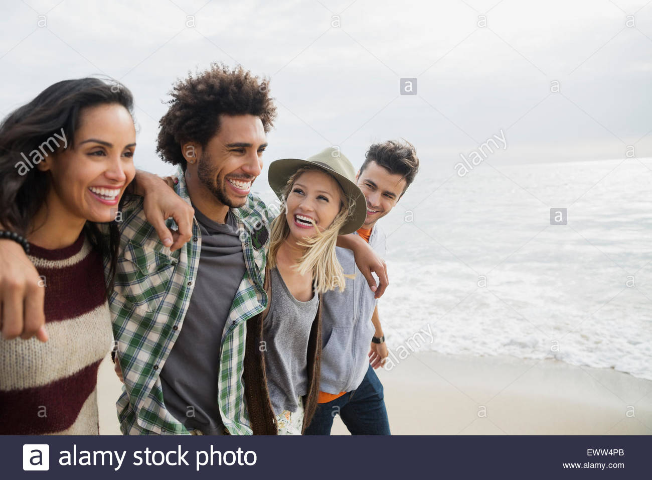 Smiling friends walking in a row on beach Photo Stock