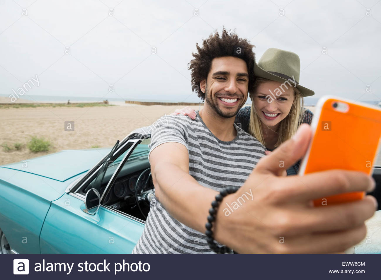 Young couple in convertible selfies at beach Photo Stock
