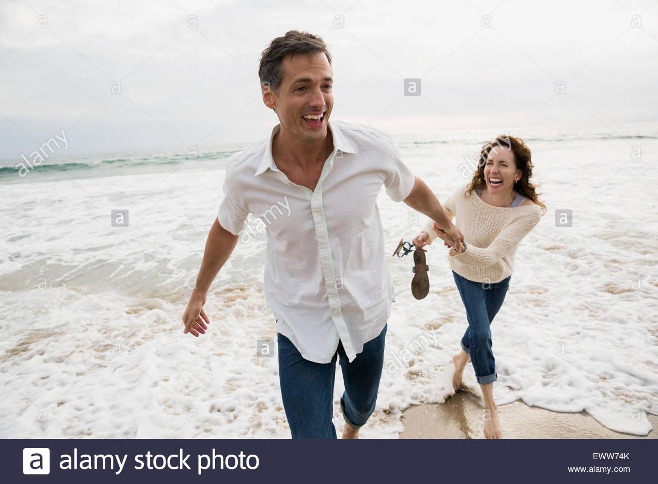 Playful couple jouant dans océan surf Photo Stock