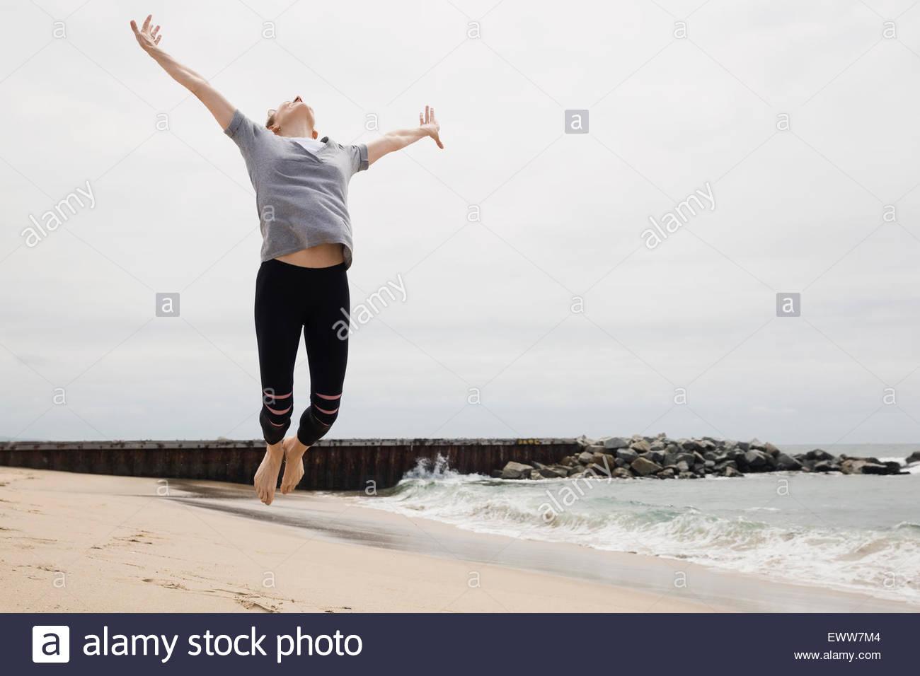 Femme exubérante, sautant de joie sur la plage Photo Stock