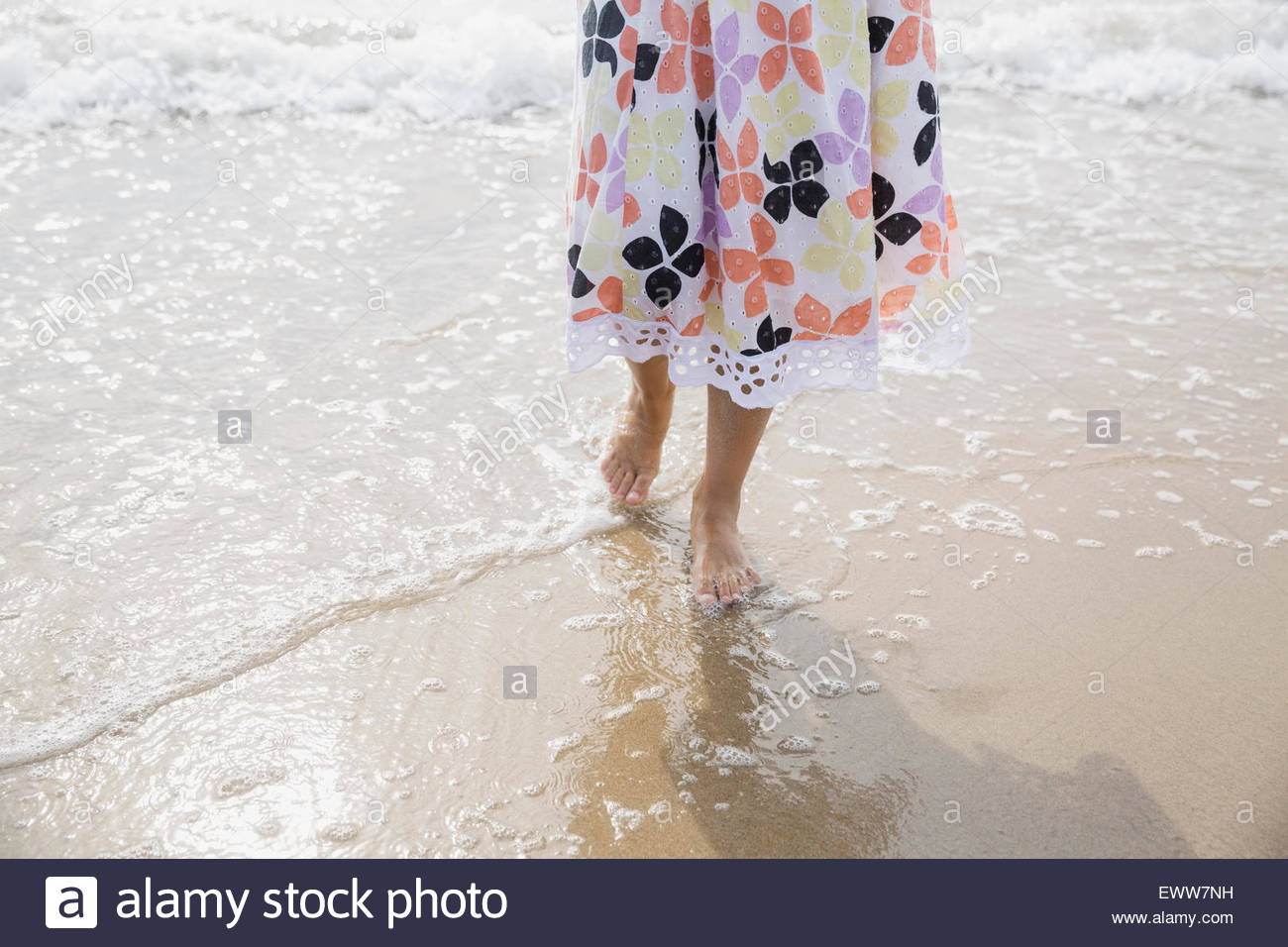 La section basse fille robe soleil pataugeant Océan surf Photo Stock