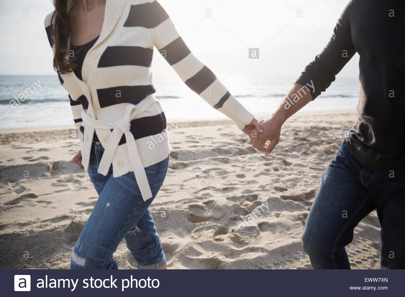 Couple holding hands and walking on beach Photo Stock