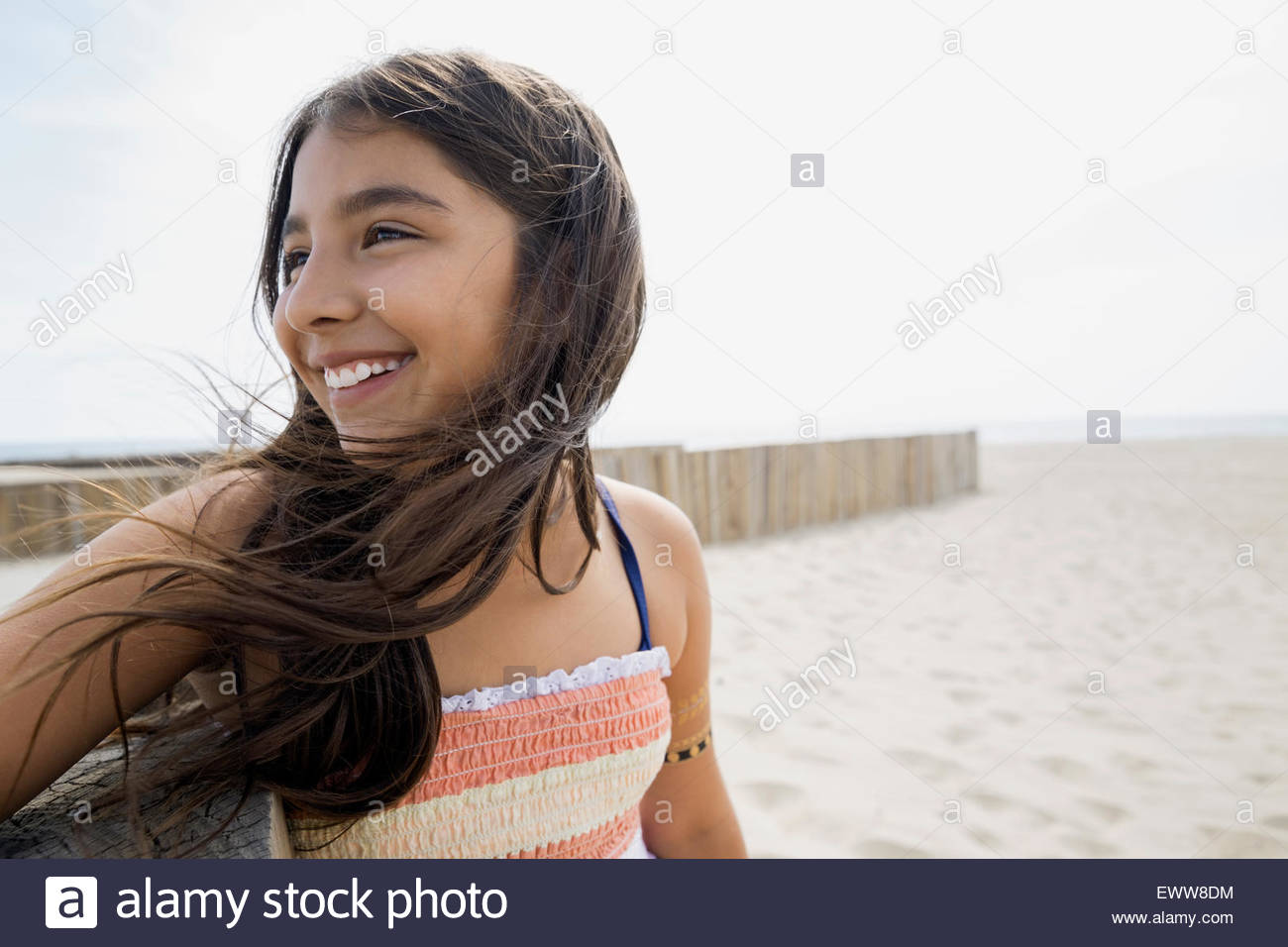 Portrait smiling girl sitting on sunny beach Photo Stock