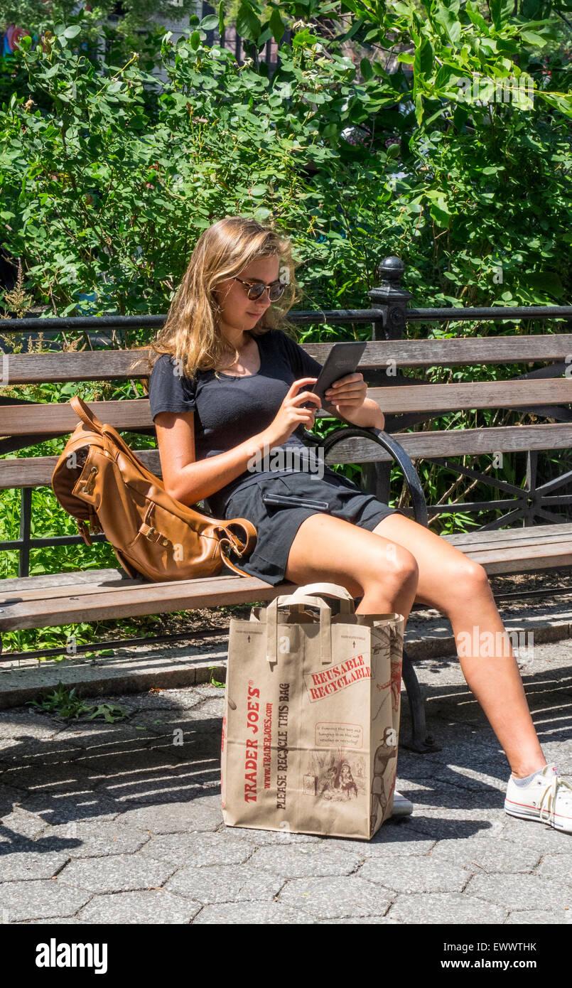 Une jeune blonde woman assise sur un banc à Union Square à New York City reading sur un e-Reader Kendle Photo Stock