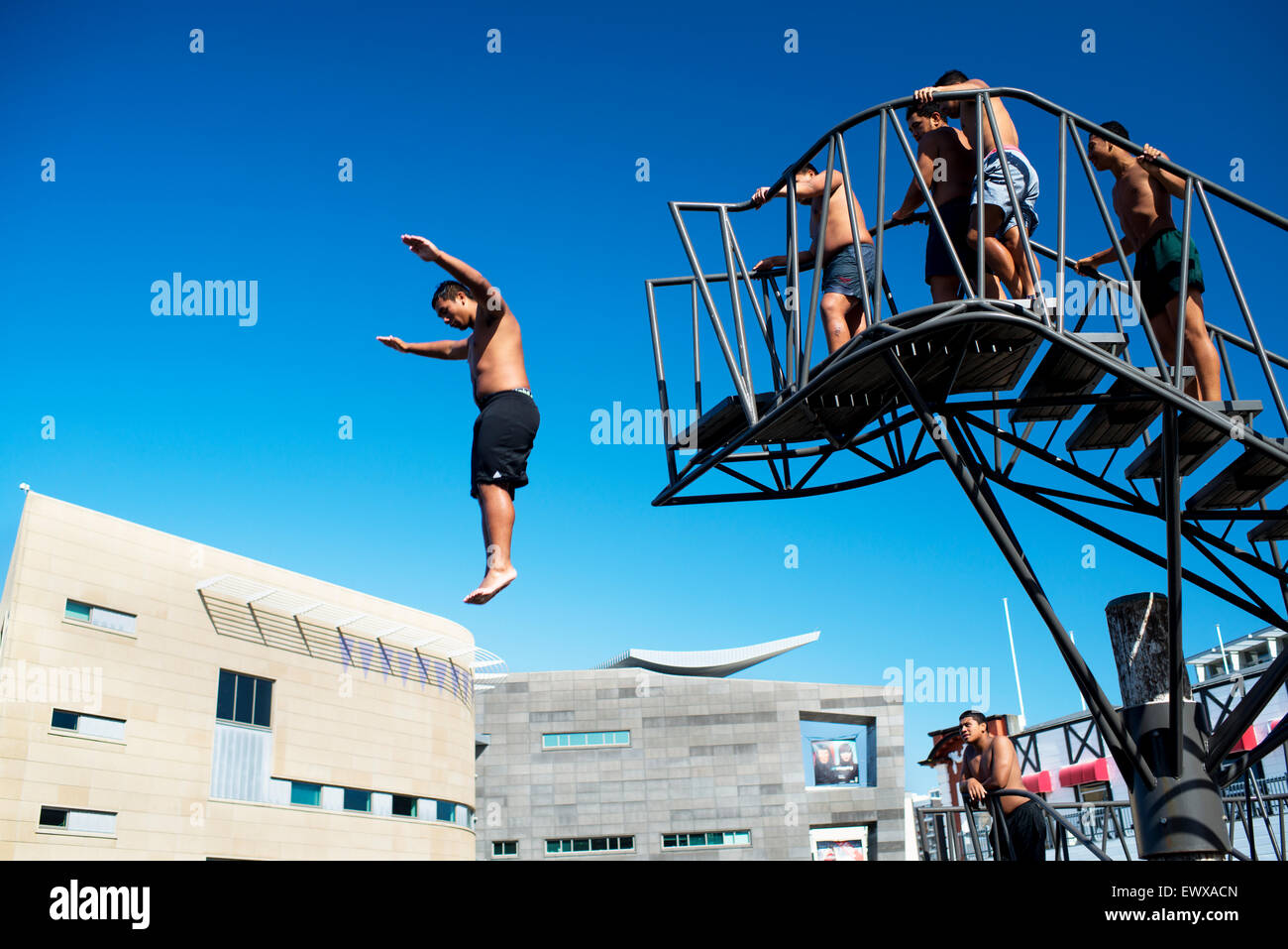 Les jeunes hommes de sauter d'une plate-forme à l'heure du déjeuner à côté de musée Photo Stock