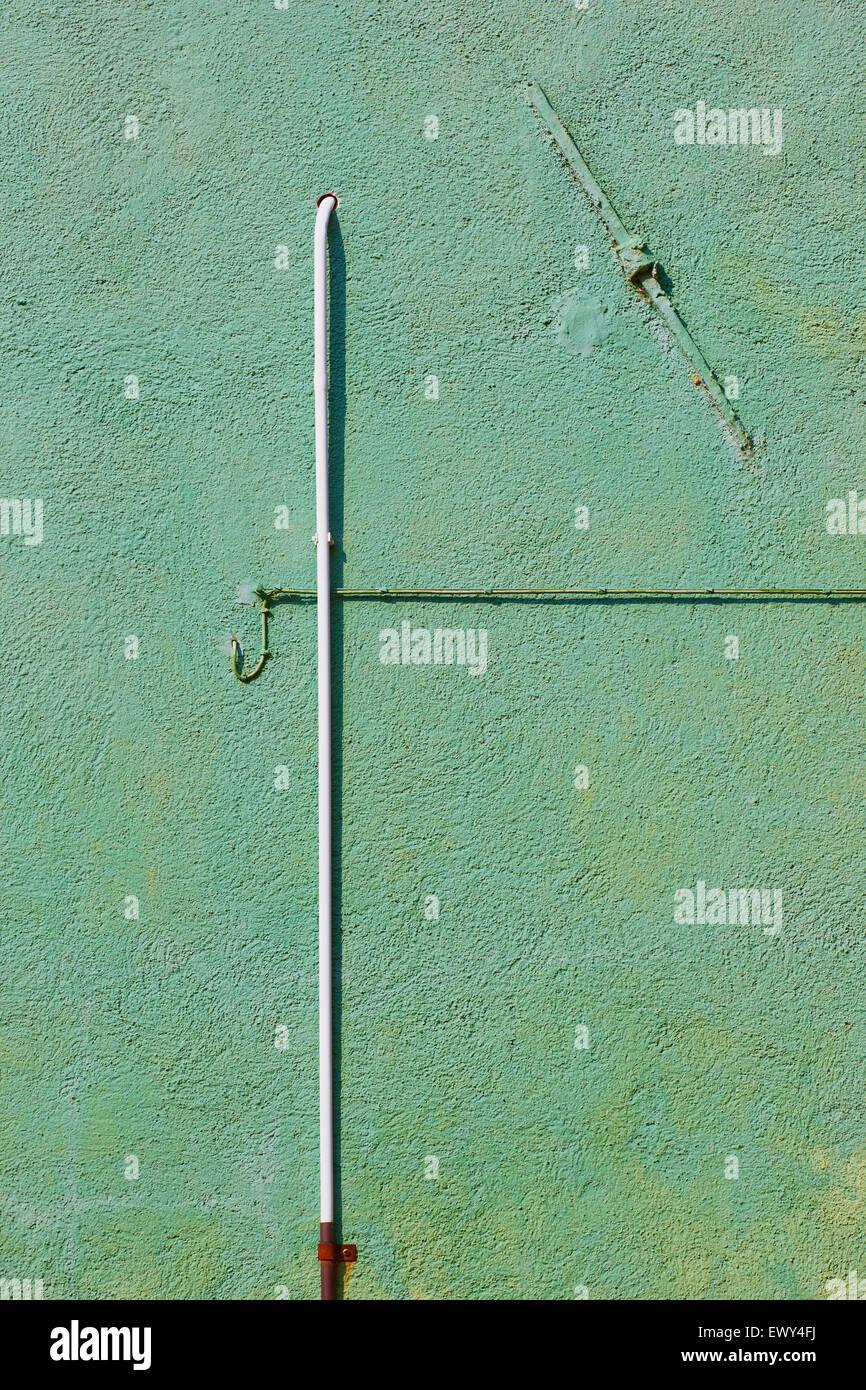 Tuyaux et les fils sur un mur vert texturé vert Burano Lagune de Venise Vénétie Italie Europe Banque D'Images