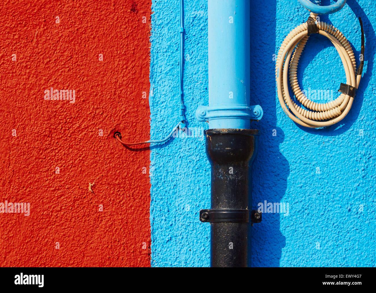Les tuyaux et les fils sur le mur de couleur rouille et bleu Burano Lagune de Venise Vénétie Italie Europe Banque D'Images