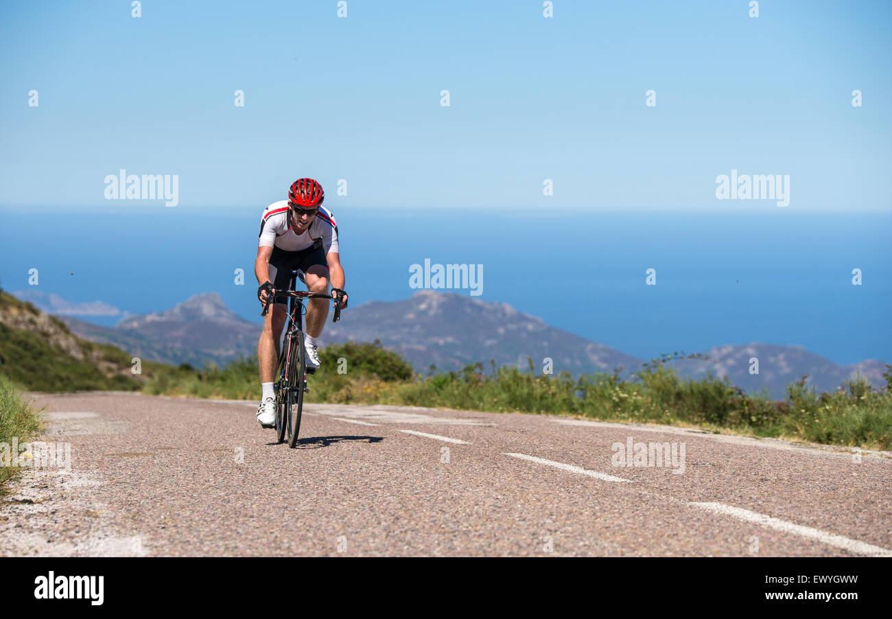 L'homme à vélo sur route, Corse, France Banque D'Images